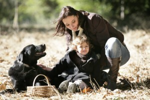 Mother & child with black labrador retriever