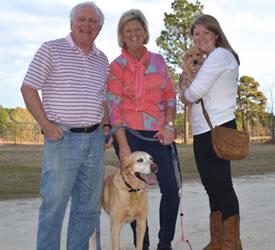 A happy family with their new Labrador retriever