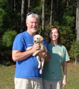 Couple with yellow Labrador retriever puppy